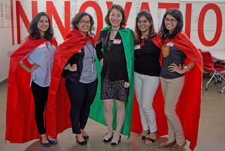 "Organizer Dr. Jing Wang (center) with caped participants at the inaugural ""UTHealth Mobile and Connected Health Hackathon"" at the TMC Innovation Institute."