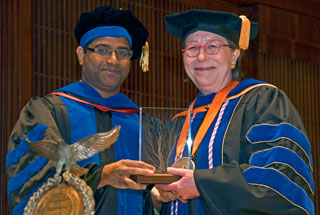 SBMI Alumnus (2015), Alumni Association member and assistant professor Deevakar Rogith, MBBS, PhD, presents the award to Dr. Johnson, May 9. (Photo by Dwight Andrews)